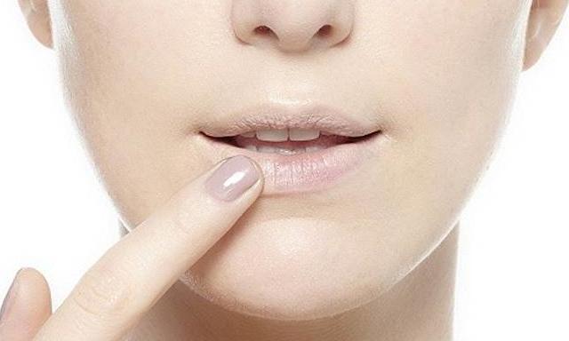 девушка наносит тональный крем на губы
